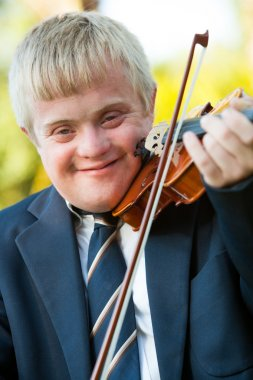 Close up portrait of handicapped boy with violin.