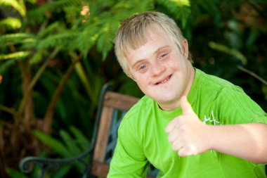 Cute handicapped boy showing thumbs up outdoors.
