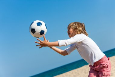 Boy playing with ball on beach.