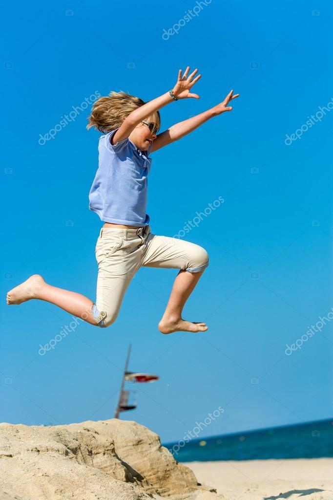 Boy jumping high on beach.
