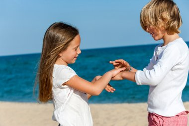 Boy and girl playing hand game on beach.