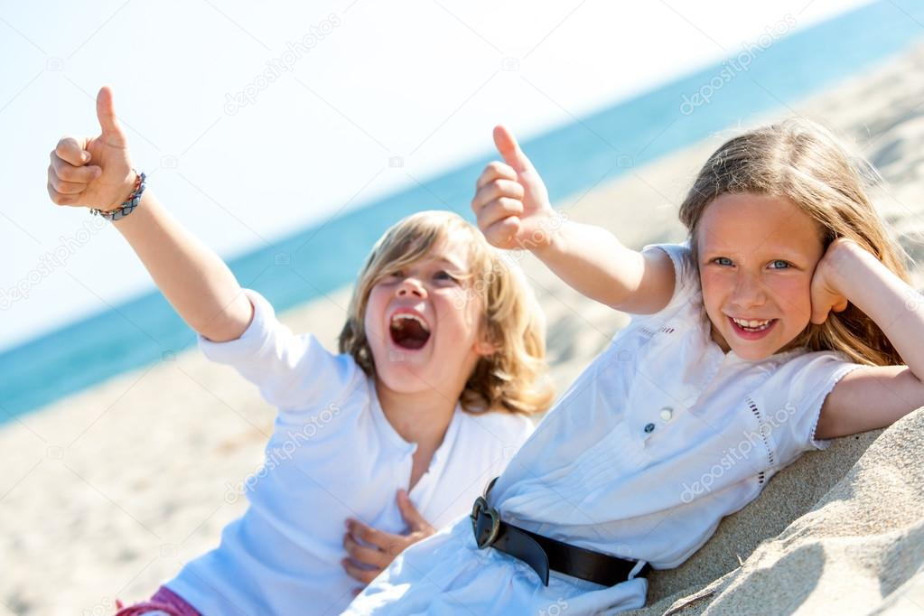 Boy and girl on beach showing thumbs up.