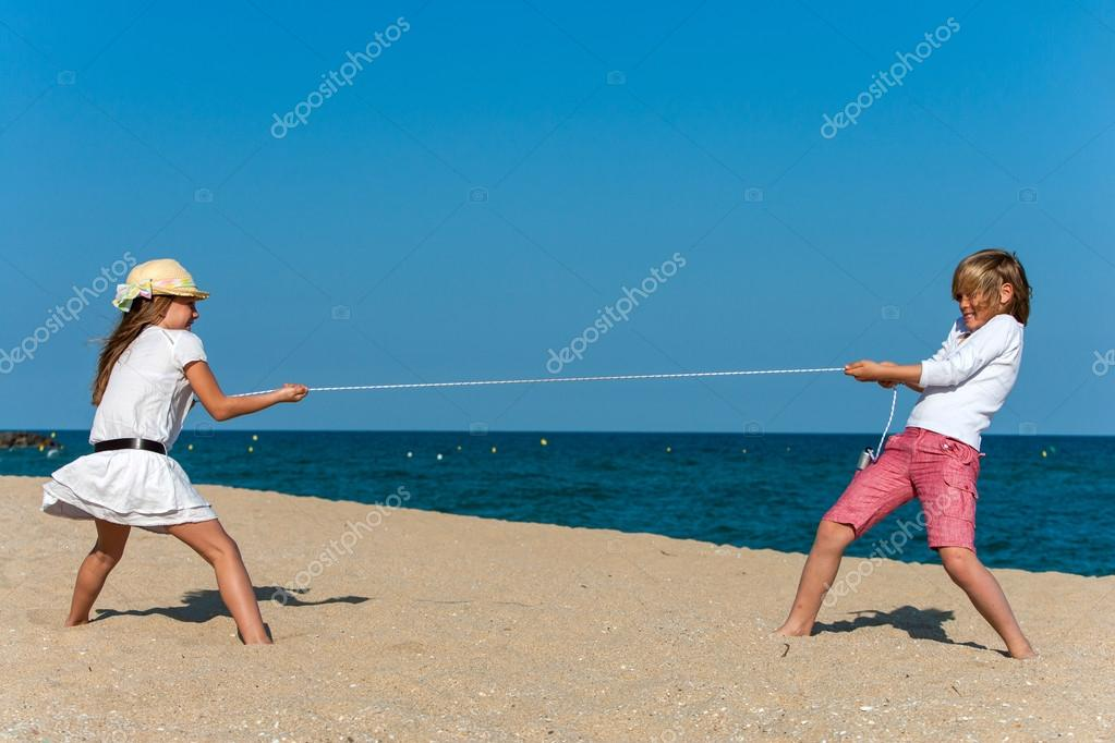 Kids having a rope war on the beach.