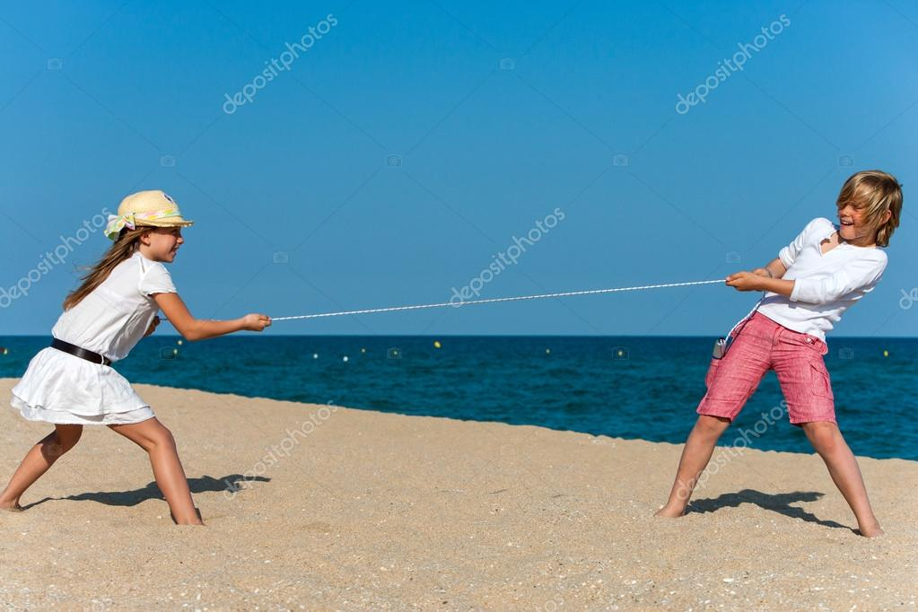 Two kids having a tug of war on beach.