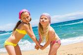 Kinder am Strand ziehen lustige Gesichter.