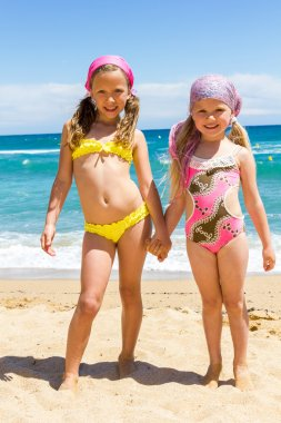 Two girls in swimwear on beach.