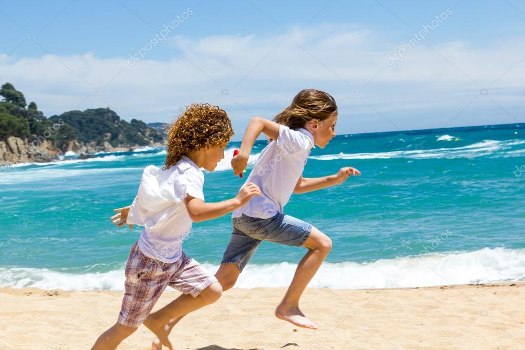Two boys running on beach.