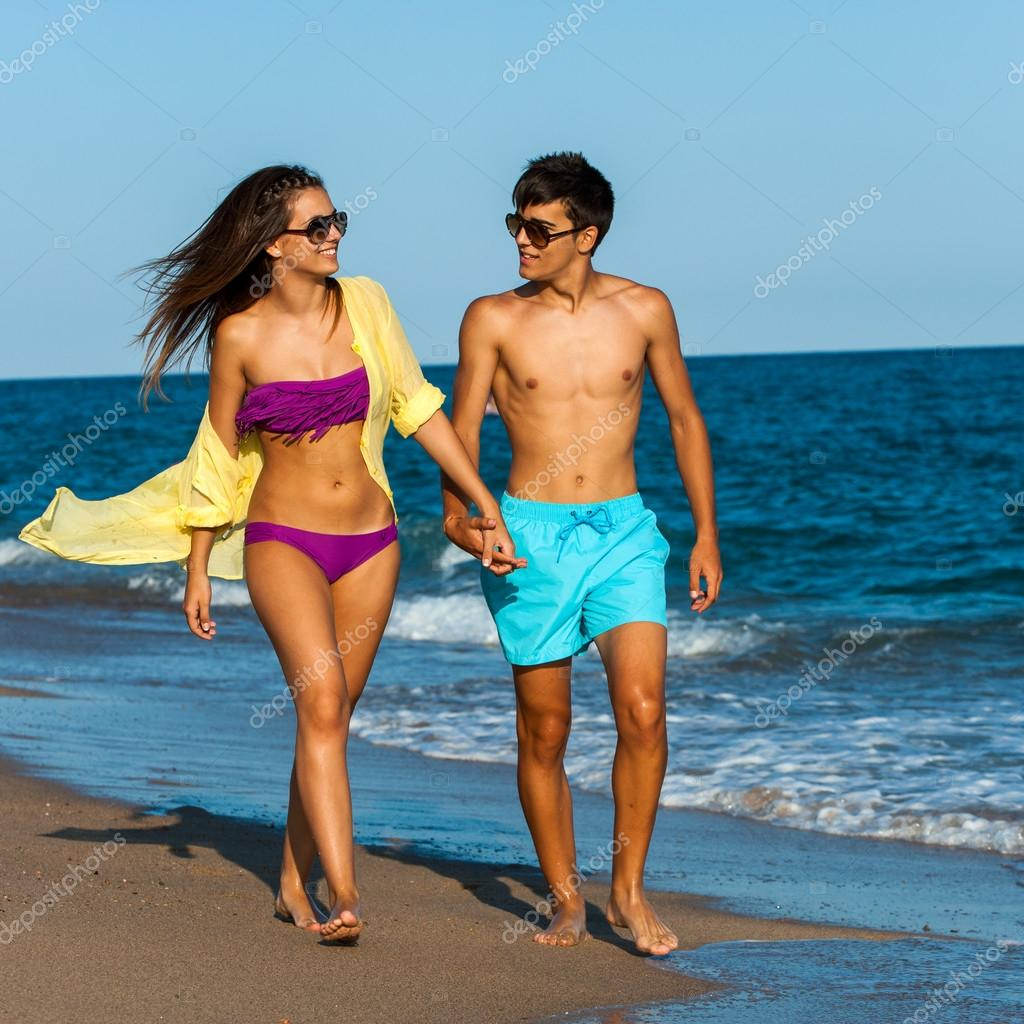 Teen couple in swim wear walking along beach.