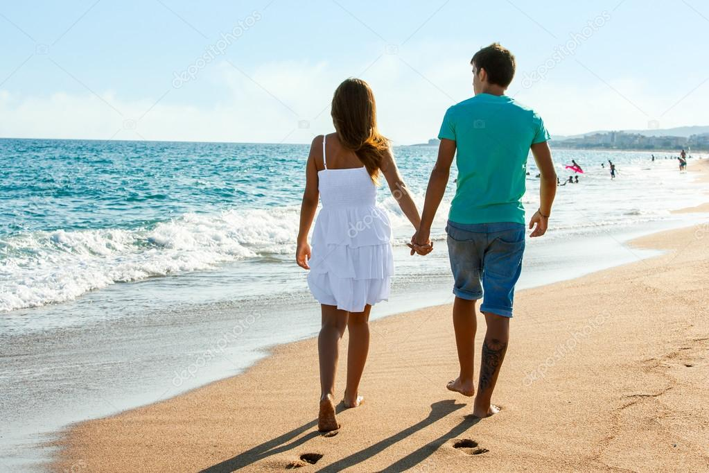 Teen couple walking away on beach.