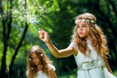 Girl waving magic wand in woods.