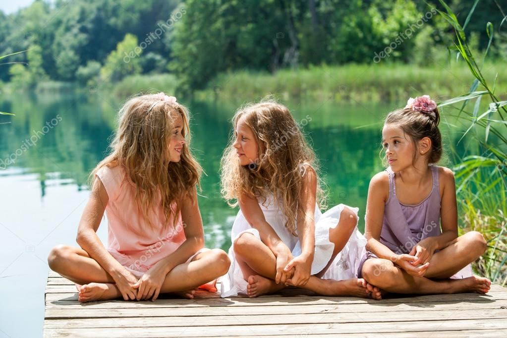 Three girl friends sitting on jetty at lake.