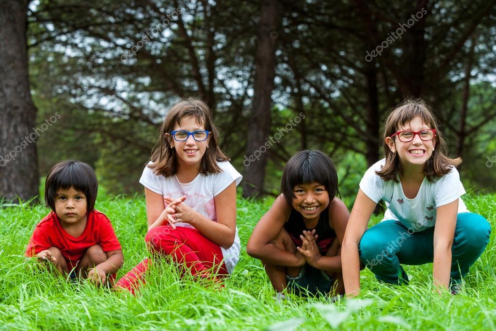 Cute girls sitting in green grass field.