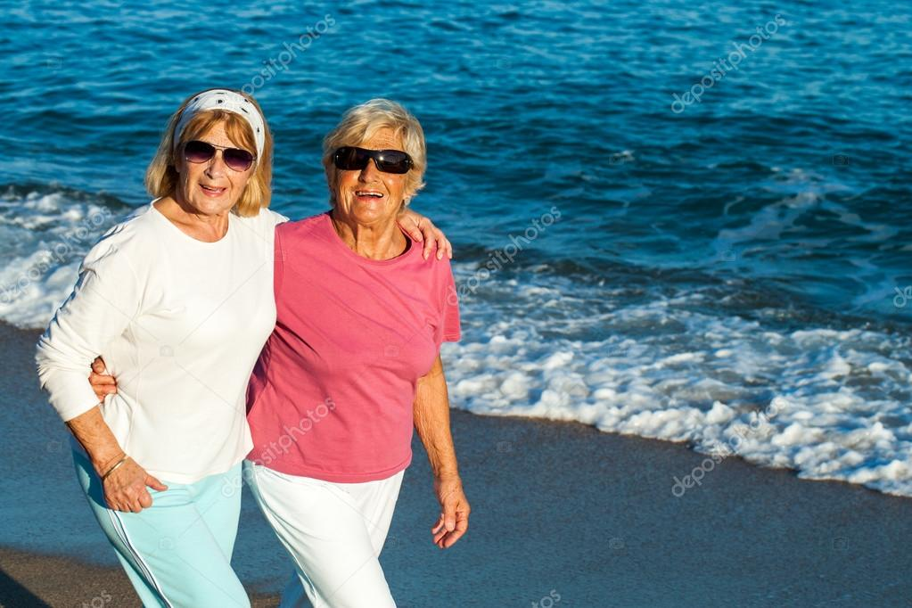 Senior female friends walking along the beach.