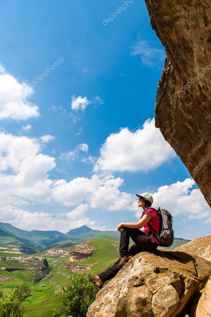 Female hiker sitting on rock.