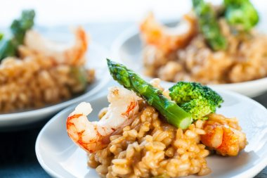 Portion of risotto rice with shrimps and asparagus.