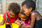 Threesome african kids having fun with tablet.