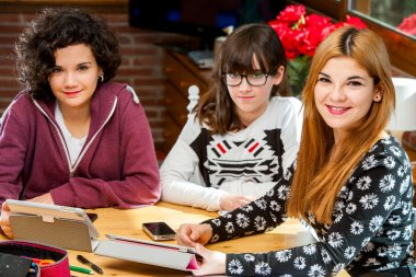 Portrait of three young female students at desk.