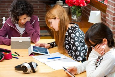 Three students working on digital devices.