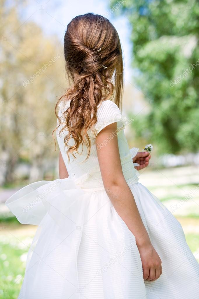 Girl in communion dress showing hairstyle.