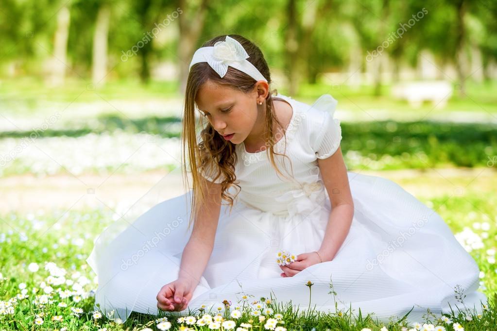 Sweet girl in white dress picking flowers.