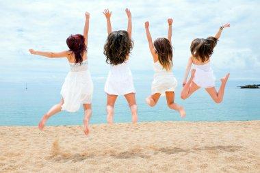 Teen girls jumping on beach