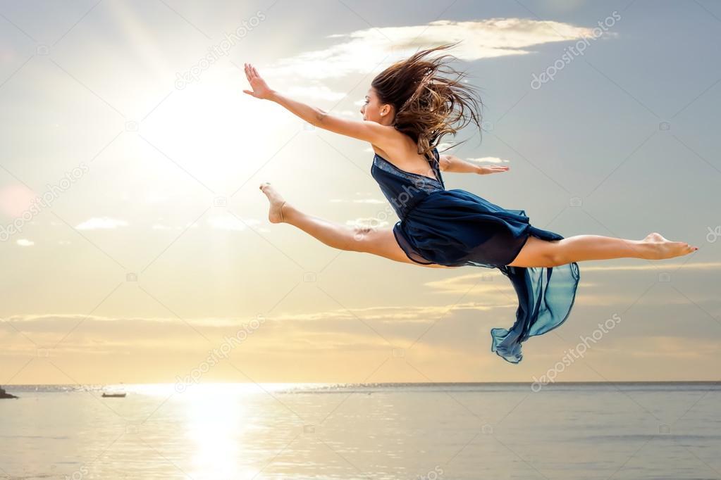 Girl doing artistic jump at sunset