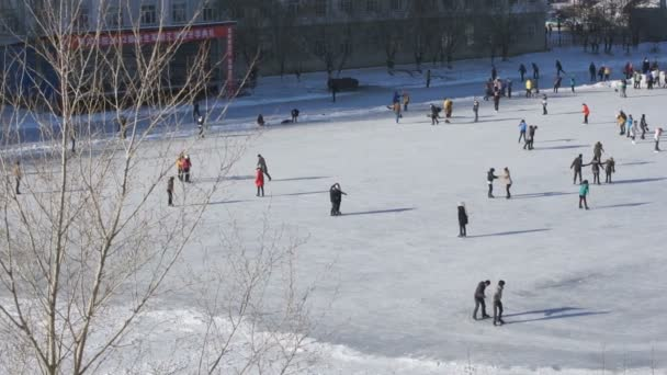 Heihe University. Chinese students on the ice skating rink (pan right)