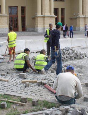 Immigrant workers from Central Asia pave a street on August 05, 2012 in St