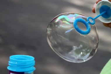 Child blowing bubbles outdoors for different uses