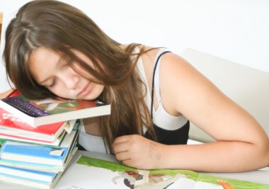 Pretty teen asleep on homework with white background
