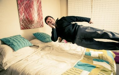 Man thinking while levitating over bed