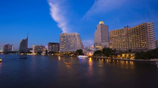 Timelapse - Stadt bei Sonnenuntergang mit beleuchteten Booten auf dem Fluss
