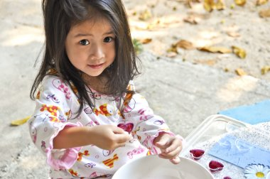 Little Asian girl making jelly.