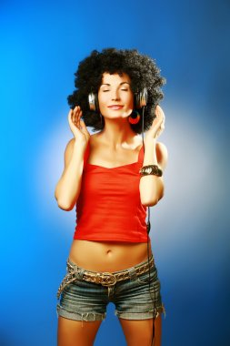 Beautiful woman with afro hair closed her eyes enjoying music with headphones .