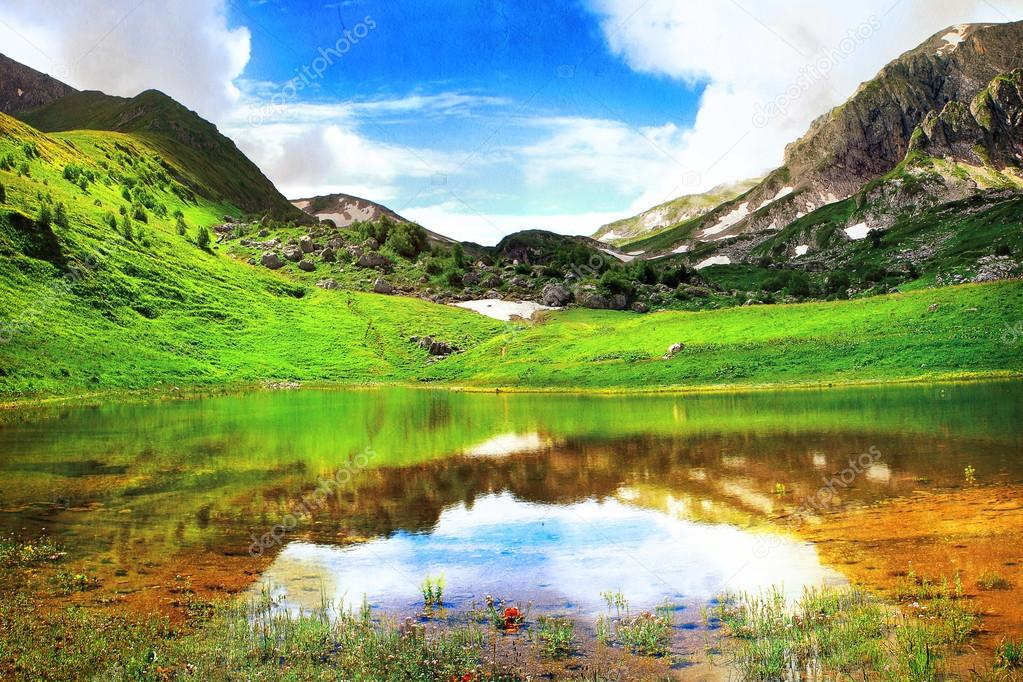Wonderful landscape with mountain lake, alpine meadow and mountains