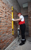 Fotografie Haus-Builder in Uniform mit einer Ebene und einem plugger