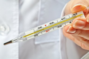 Doctor's hands showing normal temperature on thermometer