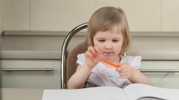 Aranyos lány rajz egy képet, és színes ceruzák