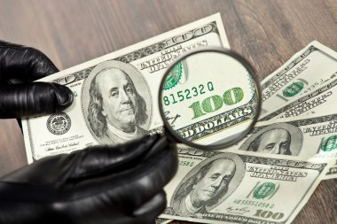 Dollar bills under a magnifying glass