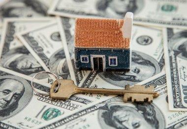 Many dollar banknotes, key and a house model