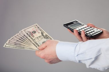 Businessman's hands holding dollar banknotes and calculator