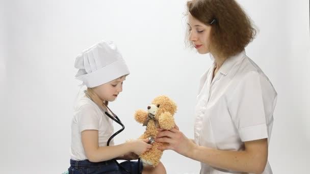 Doktor hrát s malou pacienta s hračkou a stetoskop