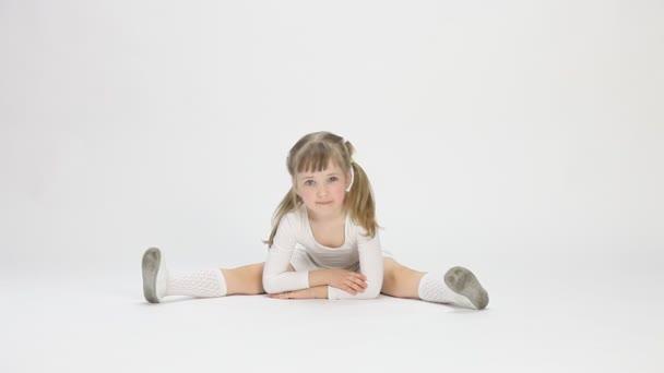 hezká holčička, sedí na podlaze a dělat cvičení