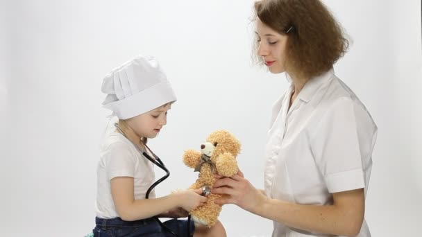 Arzt spielt mit kleinem Patienten mit Spielzeug und Stethoskop