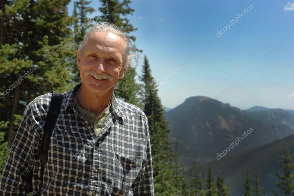 Smiling middle aged man near trees, mountains