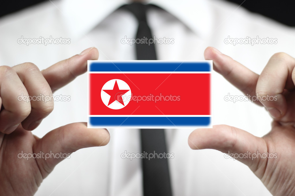 Businessman holding a business card with a north korea flag stock businessman holding a business card with a north korea flag photo by promesastudio reheart Images