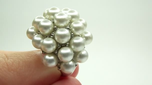 Jewelery ring with pearl crystals putting on the finger