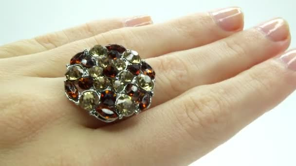 Jewelery ring with bright gem crystals putting on the finger