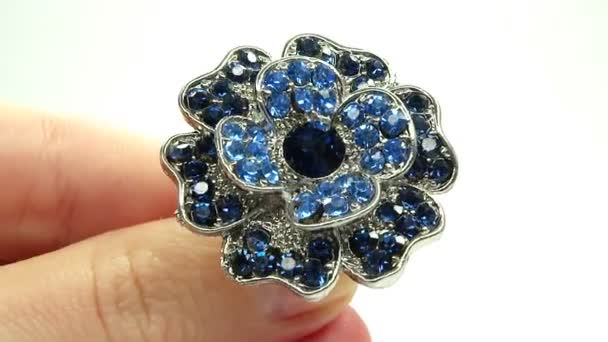 Jewelery ring with blue sapphire crystals putting on the finger