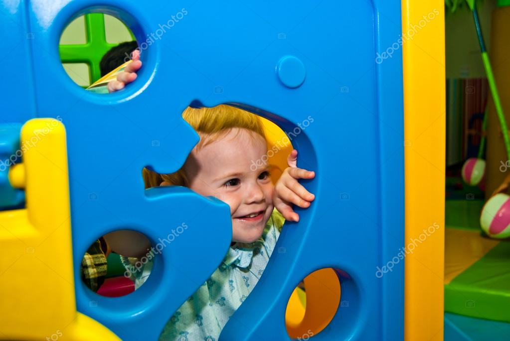 Girl 1,5 years old peeps out through the holes of game complex